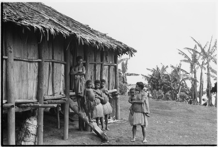 Tinami, inland Bunabun women and children next to building, probably mission clinic