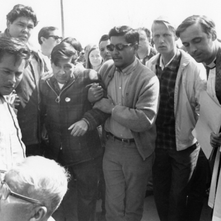 Pete Cardenas, Gilbert Flores, Cesar Chavez, Richard Chavez, & LeRoy Chatfield escort Cesar to his chair at the close of the Fast For NonViolence.