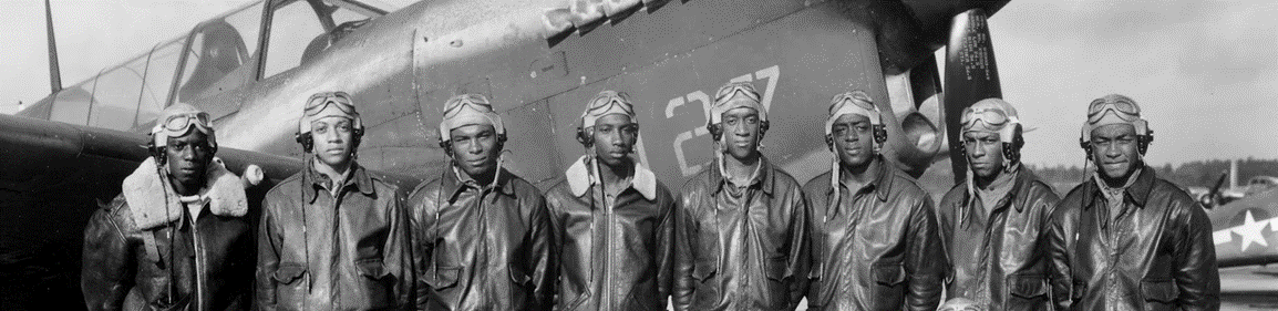 A group of Tuskegee Airmen in uniform standing in front of a military plan