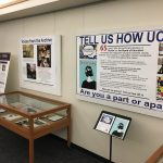 a picture of the exhibit area include canvas panels on the wall featuring items from the archive, display cases highlighting the brown vs board of education court case, and campus timeline banners