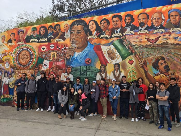 group picture of class in front of mural at Chicano Park, San Diego