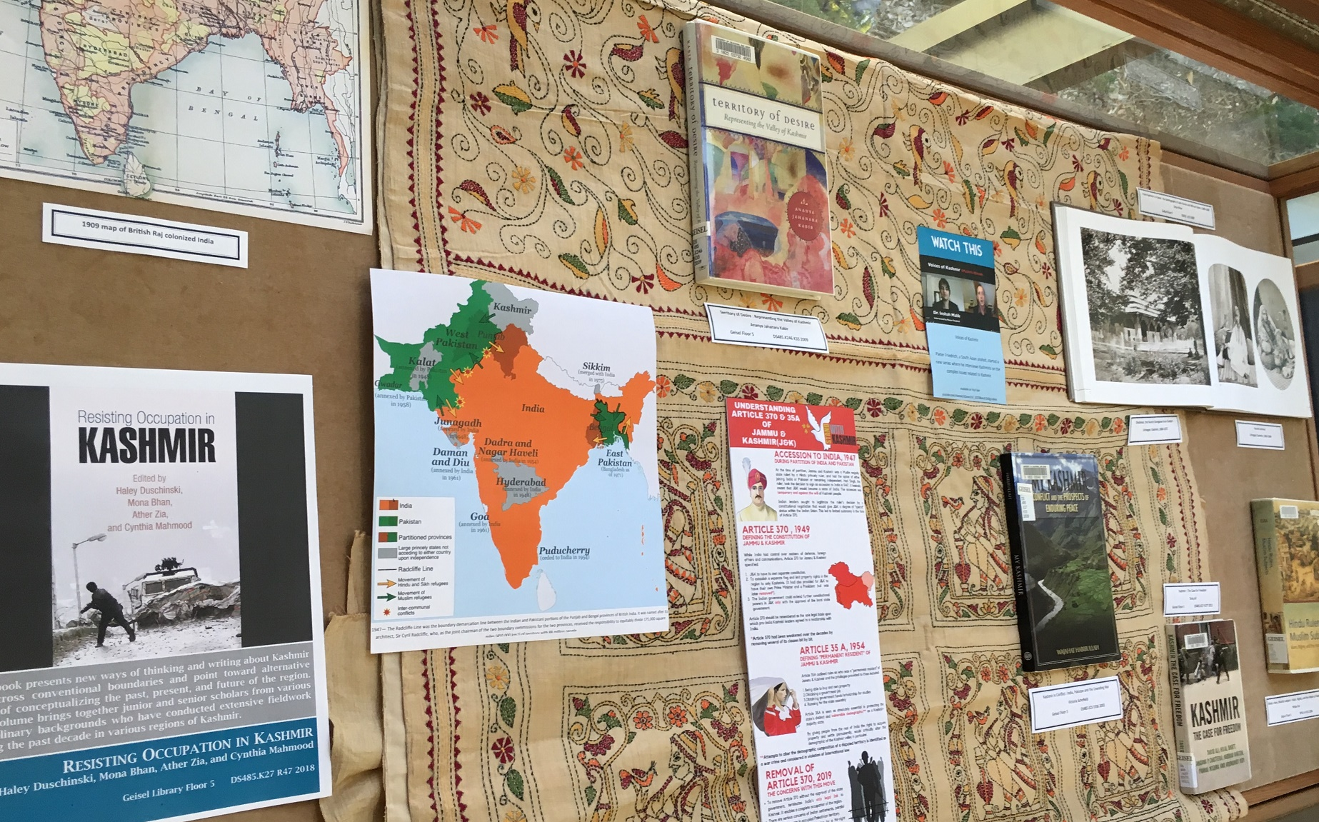 display case with maps and books related to india and kashmir