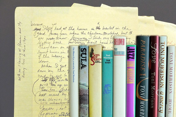 yellow pad with writing and set of books by toni morrison lined up