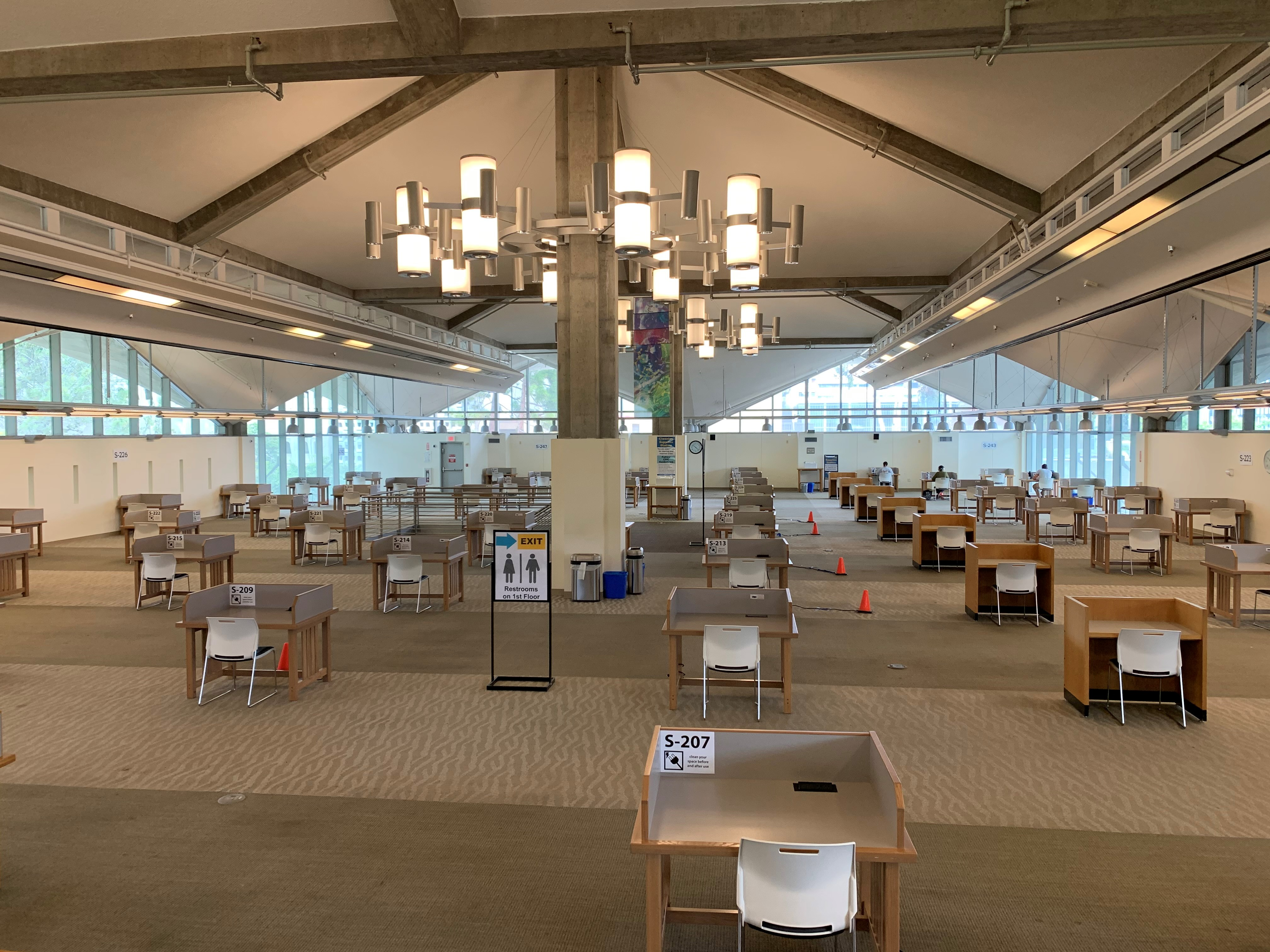 image of large open-floorplan building with individual desks spaced out 6 feet apart.